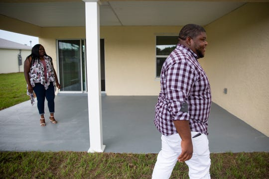 Gregory and Kortney Cosby explore their new backyard as they look over their new home, Wednesday June 12, 2019, in Fort Myers.