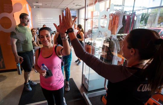 Class participants high five their coach, Nicole Brandi-Newmark Katie Kilgore prior to the start of their fitness class at Orange Theory Fitness in Cape Coral, June 4, 2019. The franchise recently opened its first Cape location.