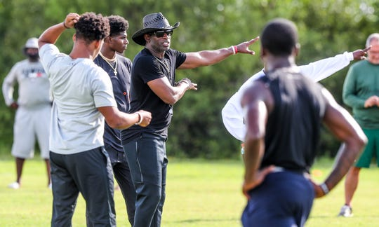 Hall of Famer and North Fort Myers alum Deion Sanders runs practice for the Lee County All-Stars on Thursday at Dunbar High School in Fort Myers, FL. Sanders brought two of his 7-on-7 football teams from Texas to play against the Lee county players as well as a team from Mississippi.