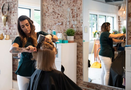 Alicia Whitworth, owner of Trade Co. Salon and Spa, curls Jennifer Barrett's hair Wednesday, June 12, 2019.