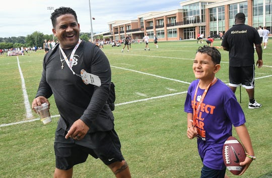St. John Bosco High School (California) linebackers coach Terry Bullock, left, and his son Braelyn watch players practice during the Dabo Swinney Football Camp in Clemson Wednesday.
