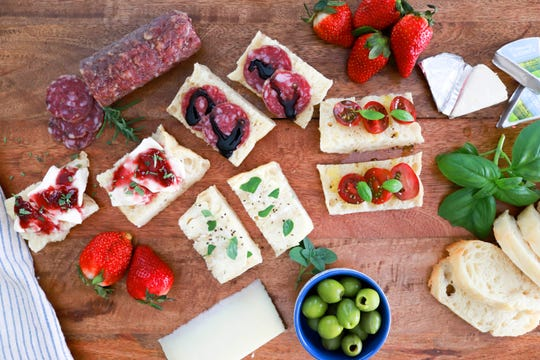 Crostini spread with meats, cheeses and fruit.