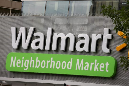 The Walmart logo is displayed above a Walmart Neighborhood Market store on Aug. 15, 2013, in Chicago.