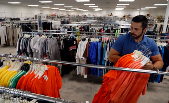 Ohio Thrift employee Kevin Tehranchi organizes T-shirts on racks Wednesday afternoon, June 12, 2019, at the new store in Lancaster.