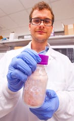 Brett Janis, a University of Louisville biology Ph.D. candidate, holds a jar of dehydrated blood.