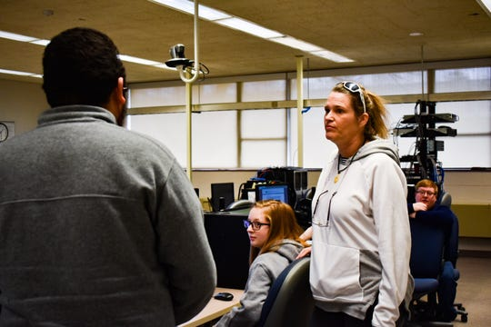 Delta College cybersecuritystudent Jerome Mendez helpsclassmate Terri Hutchins restore an Ethernet connection that ensures the computer's wired network hardware is operable.
