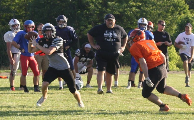 Clear Fork quarterback Jared Schaefer rollls out against pressure from Lucas defensive end Rylan Wallace as South head coach Scott Spitler of Lucas looks on during all-star practice Tuesday at Lexington High School.