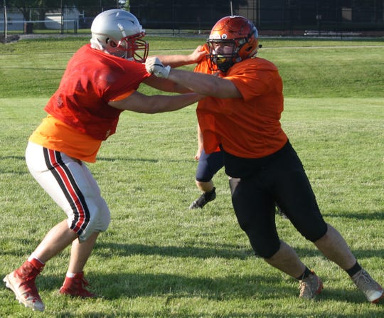 Lucas defensive end Rylan Wallace, right, tries to shed a block during the South's all-star practice on Tuesday at Lexington High School.