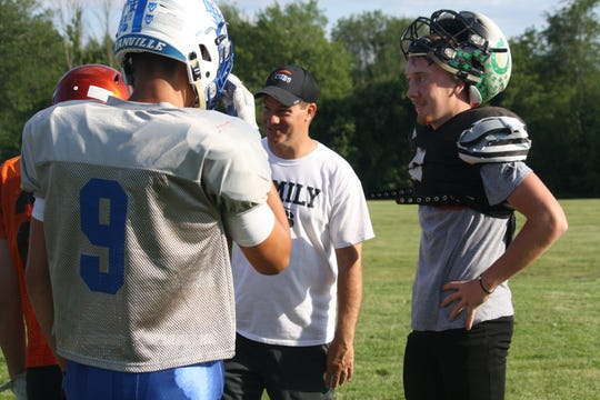 Clear Fork quarterback Jared Schaefer,  right, and some of his fellow South all-stars enjoy a break from drills during practice Tuesday at Lexington High School.