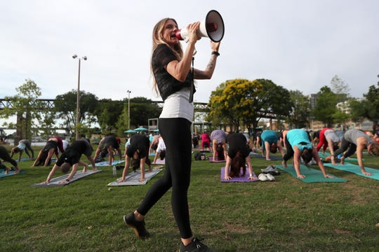 Yoga instructor Charlie Hayden leads a class along the riverfront in Downtown Memphis on Tuesday. The free class has grown in numbers over the years to include a few hundred participants.