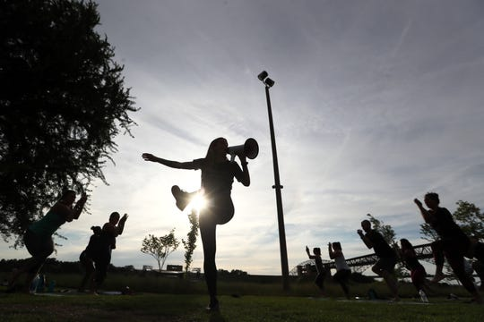 Yoga instructor Charlie Hayden leads a class along the riverfront in downtown Memphis on Tuesday. The class has grown in numbers over the years to include a few hundred participants.