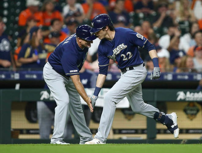 Brewers rightfielder Christian Yelich celebrates with Ed Sedar after hitting his 25th home run.