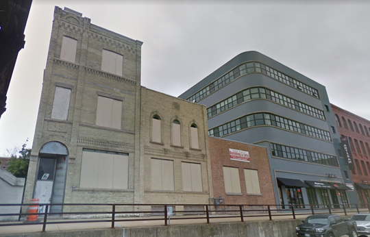 A large, three-story building (left) in Walker's Point that was previously planned for an office redevelopment has been sold.