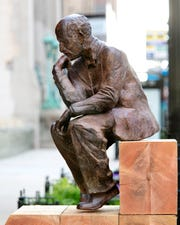 """Pensive"" by Radcliffe Bailey which can be seen at 500 E. Wisconsin Ave. as part of Sculpture Milwaukee 2019. Bailey's sculpture casts activist W.E.B. Du Bois in the pose of Rodin's 'The Thinker."""