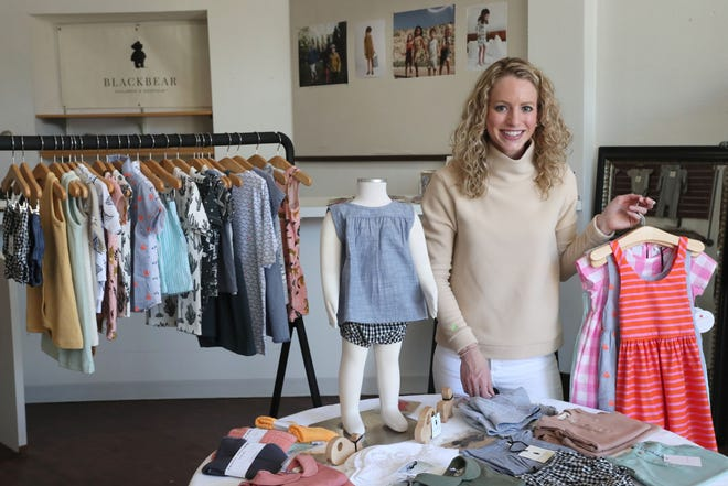 Owner Emma Carollo holds some of the clothing available at Blackbear Children's Boutique, a pop-up storefront that opens June 14 at 2622 North Downer Ave.