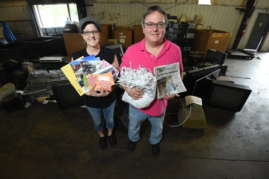 Plant Manager Kelly Shrake, left, holds up the type of paper the Baxter Recycling Center will no longer accept after July 1 while Executive Director Paul Neal holds up the type of paper the center will accept.