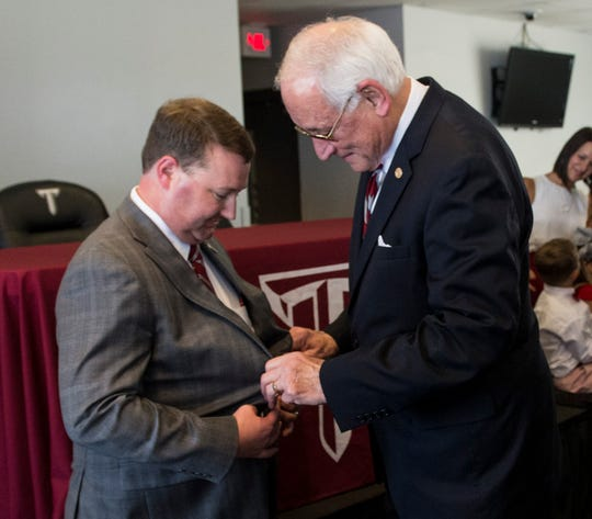 New athletic director Brent Jones gets help from Chancellor Dr. Jack Hawkins during his introductory press conference at Troy football stadium  in Troy, Ala., on Wednesday, June 12, 2019.