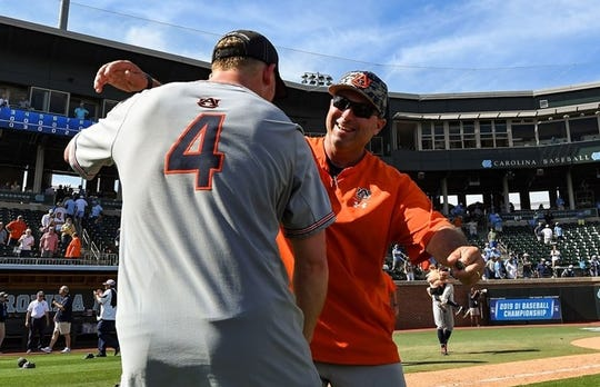 Auburn coach Butch Thompson (right) embraces first baseman Rankin Woley (left) after a super regional win over North Carolina on June 10, 2019, in Chapel Hill, NC.