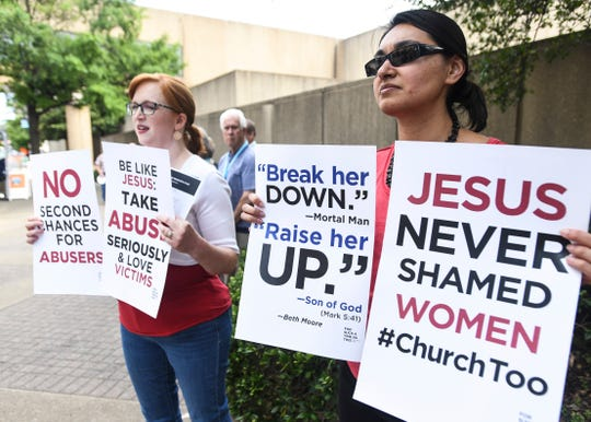 Jennifer Weed, left, and Nisha Virani, both of Birmingham, Ala., demonstrate outside Southern Baptist Convention's annual meeting Tuesday, June 11, 2019, during a rally in Birmingham, Ala. The For Such A Time As This protest calls for a change in the way the SBC views and treats women and demands action to combat sexual abuse within the establishment. (AP Photo/Julie Bennett)