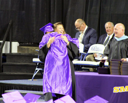 Smyrna High Principal Sherri Sutherland embraces graduate Mohammad Tantawi during the 2019 graduation ceremony at Murphy Center.