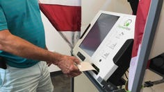 A resident uses the new ballot marking machine during a voting demonstration event on June 12, 2019.
