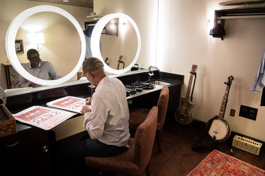 Keb' Mo' signs posters in his dressing room before a concert at the Franklin Theatre in Franklin, Tenn., Friday, June 7, 2019.