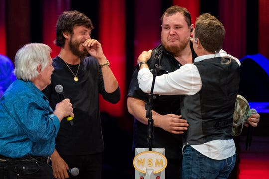 Luke Combs gets emotional after being surprised by John Conlee, Chris Janson and Craig Morgan, from left, with his invitation to join the Grand Ole Opry at the Grand Ole Opry Tuesday, June 11, 2019, in Nashville, Tenn.