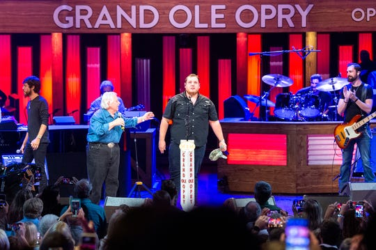 Luke Combs, center, is surprised by John Conlee, Chris Janson and Craig Morgan with an invitation to join the Grand Ole Opry on June 11, 2019, at the Grand Ole Opry House in Nashville.