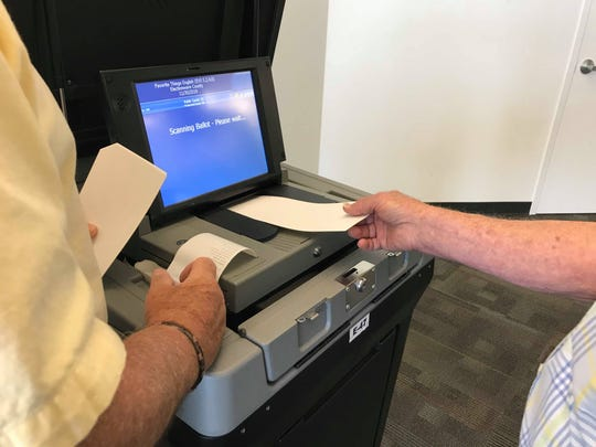A paper ballot is scanned using one of the new machines at a voting demonstration event on June 12, 2019.