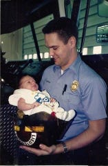 Jeff Hussey, who now serves as Ohio State Fire Marshal, holds his son, Ryan Hussey, in 1992. The younger Hussey, now 27, works as a firefighter for Granville Township Fire Department.