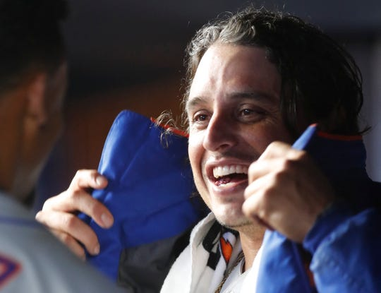 New York Mets starting pitcher Jason Vargas smiles in the dugout as he dons his jacket during the team's second game of a doubleheader against the New York Yankees, Tuesday, June 11, 2019, in New York. Vargas pitched six innings, allowing three runs on seven hits.