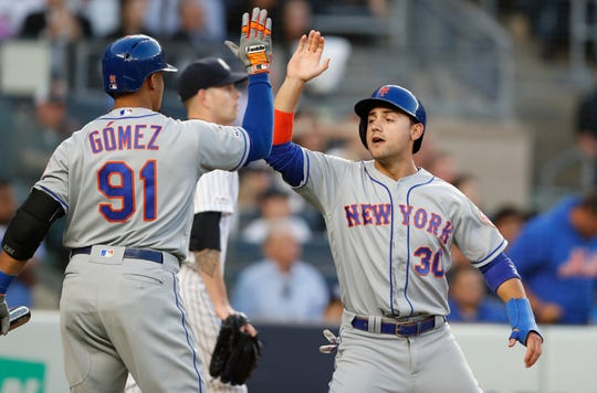 New York Mets on-deck batter Carlos Gomez (91) congratulates Michael Conforto (30) as New York Yankees starting pitcher James Paxton, center, walks back to the mound after Conforto scored on Adeiny Hechavarria's single during the third inning of the second game of the doubleheader Tuesday, June 11, 2019, in New York.