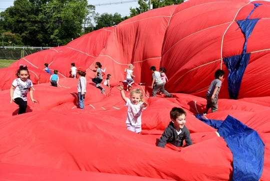 The QuickChek New Jersey Festival of Ballooning and PNC Bank inflated a 75-foot-tall air balloon for children in the Wayne Center for Family Resources to play in on Wednesday, June 12, 2019. The children help deflate the balloon.