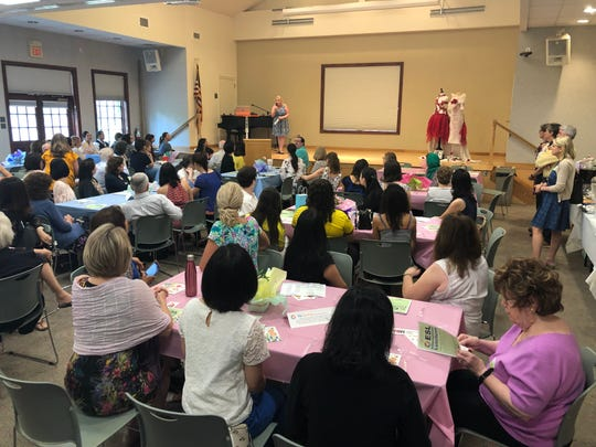 Students and tutors attend the Ridgewood Library's ESL Luncheon on June 7. On stage is Library Director Nancy Greene.