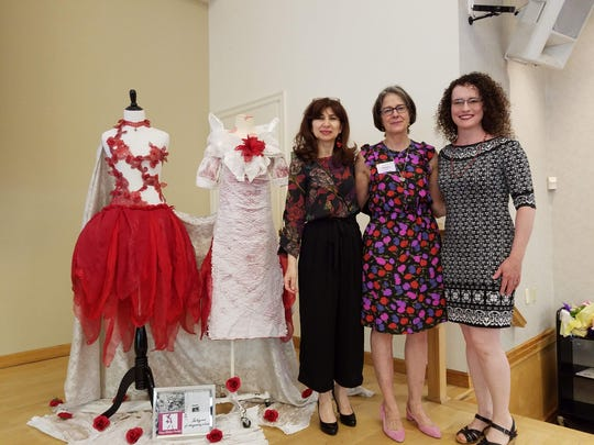 Vilma Gonzalez (left) presented on her visual merchandising and window design career during the ESL Luncheon, posing with dresses she made with recycled materials.