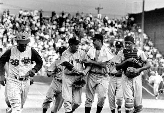 New York Yankee players congratulate pitcher Bud Daley after final out in game five to win the 1961 World Series at Crosley Field in Cincinnati, Ohio, Oct. 9.  Cincinnati Reds center fielder Vada Pinson (28), who made final out with fly ball to left, walks by at left.  The Yankees, from left, are, Daley, right fielder John Planchard, who did not play the ninth inning, first baseman Bill Skowron, and catcher Elston Howard.  A bat boy runs behind Daley.  (AP Photo)