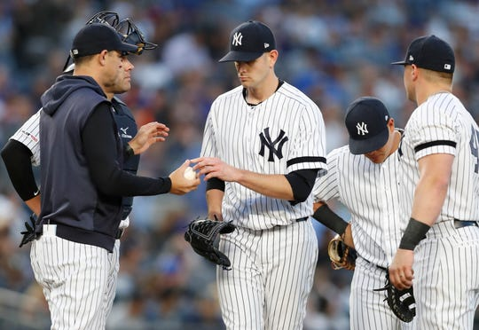 New York Yankees starting pitcher James Paxton, center, hands the ball to manager Aaron Boone, left, during the third inning of the team's second game of a doubleheader against the New York Mets, Tuesday, June 11, 2019, in New York. Yankees third baseman Gio Urshela, second from right, and and first baseman Luke Voit join Paxton and Boone on the mound. as does catcher Austin Romine, back left.