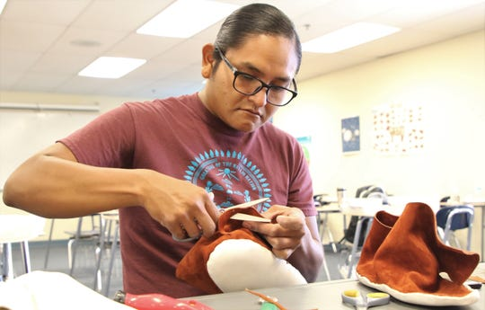 Eliseo Curley trims suede on a pair of moccasins on June 12 at the Career and Technology Education Center in Farmington.
