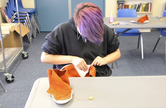 Deann Barber works on a pair of moccasins on June 12 at the Career and Technology Education Center in Farmington.
