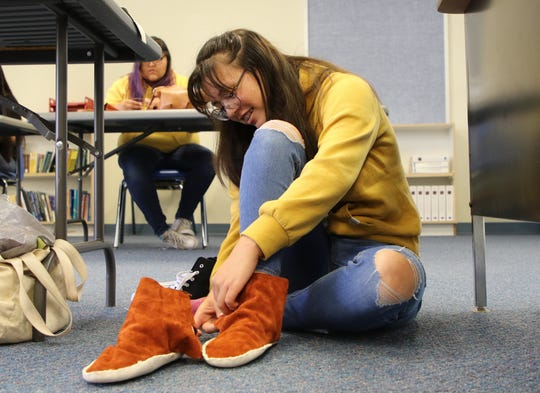 Rylee Wilkens-Clary tries on the pair of moccasins she made on June 12 at the Career and Technology Education Center in Farmington.