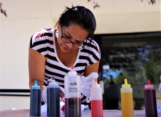 Lucy Livingston tie dyes a shirt, Wednesday, June 12, 2019 at San Juan College.