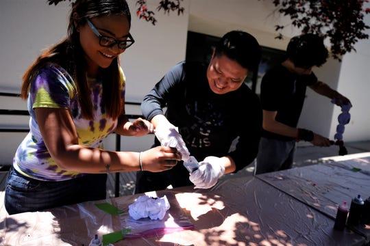 Constance Taylor shows Faron Lewis how tie dye a shirt, Wednesday, June 12, 2019, at San Juan College in Farmington.
