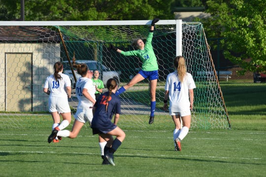 Marian goalie Megan Kraus goes up for a big save against Flint Powers Catholic in the state semifinals on June 11, 2019.