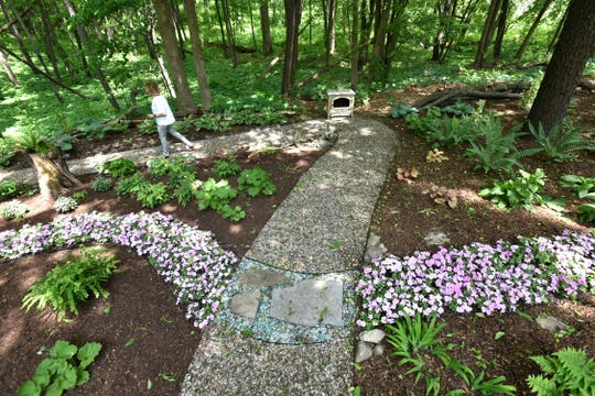 The Sabin's garden features paths of pebble stone and rivers and flowers.
