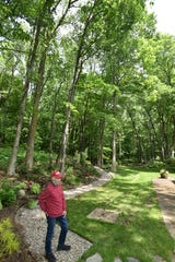 Mitchell Sabin pauses by the path that runs through his woods and garden area of his Old Milford Farms home on June 12. His garden will be featured in the Garden Walk on Sat., June 22.
