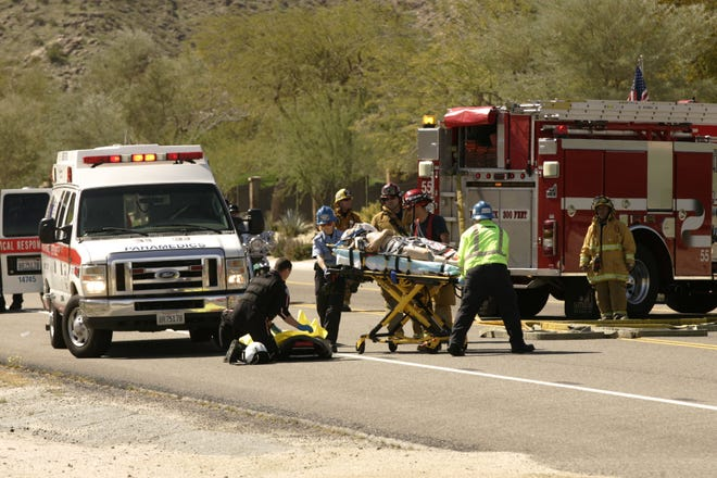 Cal-Fire/Riverside County firefighters and American Medical Response paramedics move a 78-year old male motorcyclist from an ambulance to a Reach Air Ambulance that landed at the base of Highway 74 in Palm Desert on Thursday, March 10, 2011 after the man struck three other vehicles on a bend up the mountainous highway between mile markers 88 and 89.
