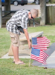 Caleb Sager, 11, is in awe of the vibrant red in the American flags at Navarre Park on Wednesday. Both Caleb and his mother, Judy Sager, have color vision deficiency. Caleb explained that prior to getting his EnChroma glasses, the red stripes looked brown to him.
