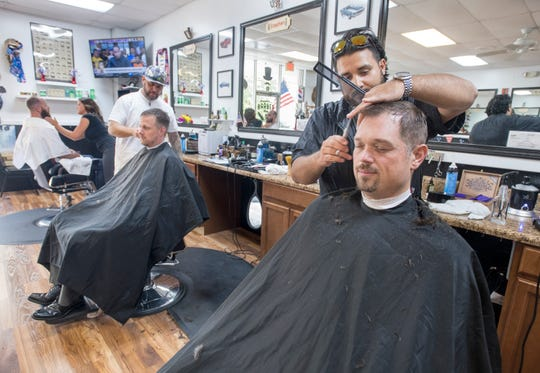 Richard Rodriguez cuts Justin Roads' hair at Armando's Barber Shop along Nine Mile Road in Pensacola on June 12.