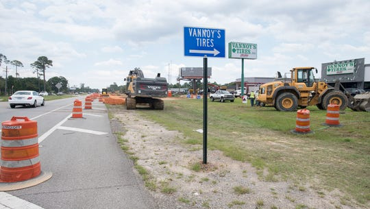 A blue sign helps customers find their way into Vannoy's Tires amid the construction along Nine Mile Road in Pensacola.