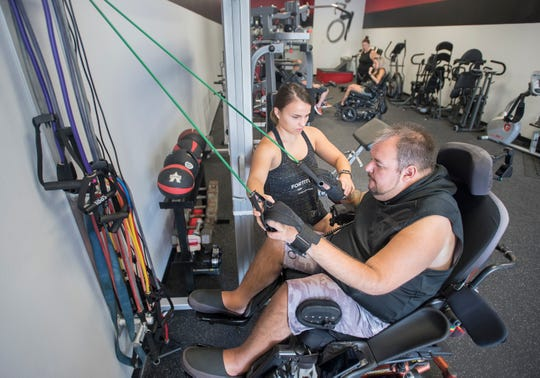 Personal trainer Emily Lawrence works with Spencer Blomquist on June 12 at The Seven Project Adaptive Fitness along Nine Mile Road in Pensacola.